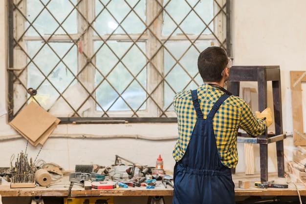 Tuttofare che fa mobili in legno in officina