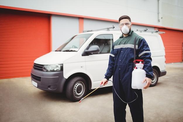 Tuttofare con insetticida in piedi davanti al suo furgone