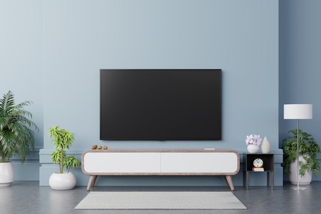 Tv sul mobile in soggiorno moderno hanno piante e libro su sfondo blu muro.
