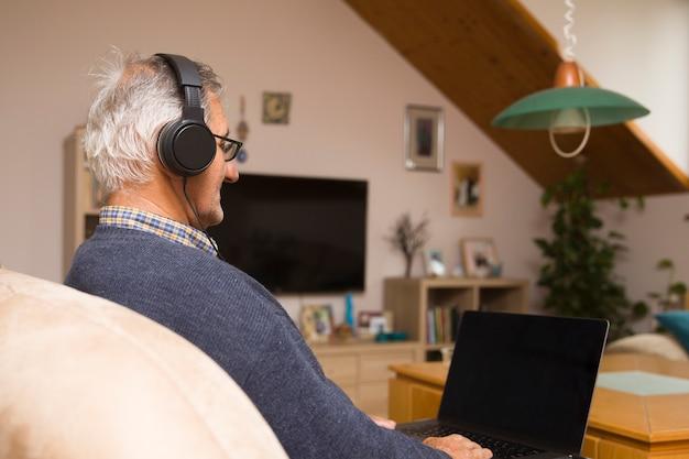 Ubicazione dell'uomo anziano moderno a casa con gli auricolari e la videochiamata online