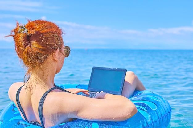 Ubicazione della donna nell'anello gonfiabile in mare e nel funzionamento in computer portatile.