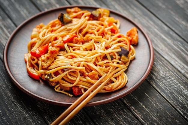 Udon mescolare frittura noodles con carne e verdure in salsa e bacchette su fondo di legno nero
