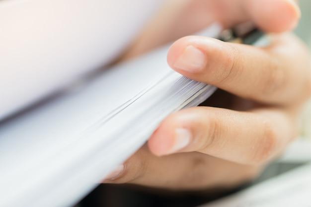 Uffici della donna di affari che lavorano per l'organizzazione della pila non finita dei documenti delle carte del documento con la penna