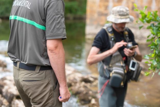 Ufficiale di polizia o guardia forestale che controlla la licenza del pescatore in fiume. ispezione della pesca. legge.