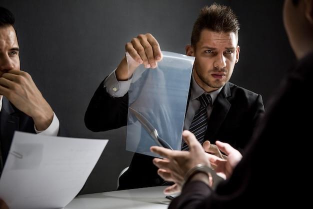 Ufficiale nella stanza degli interrogatori che mostra un coltello come prova dell'omicidio