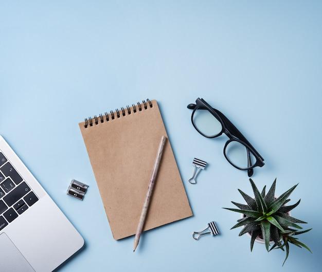 Ufficio a casa. piatto business laici con notebook, nota artigianale, penna, occhiali e succulente su sfondo blu