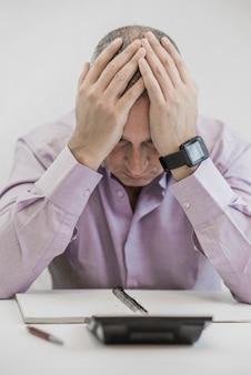 Ufficio, affari, tecnologia, finanze e concetto di internet - stressato uomo d'affari con computer portatile e documenti in ufficio