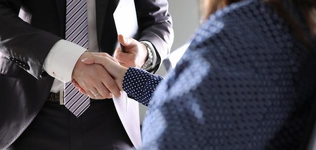 Ufficio dell'interno di scossa della mano della donna e dell'uomo d'affari