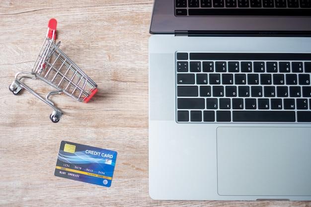 Ufficio della carta di credito e del computer portatile del carrello a casa. affari, e-business, tecnologia, commercio elettronico, digital banking e concetto di pagamento online