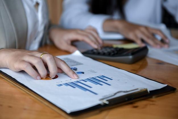 Ufficio della ragazza utilizzando una calcolatrice per analisi di grafici.