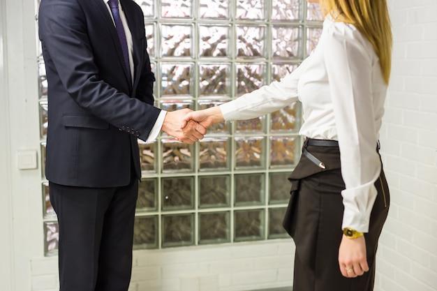 Ufficio di and businesswoman shaking hands in dell'uomo d'affari