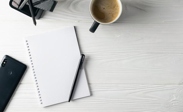 Ufficio di cancelleria aziendale tra cui caffè, notebook, penna, telefono in testa piatta laici