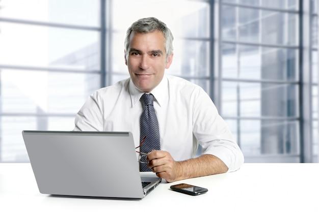 Ufficio di lavoro interno moderno senior dell'uomo d'affari