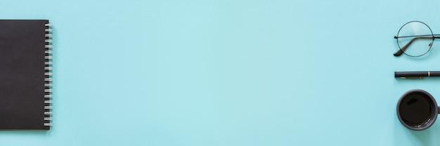 Ufficio o casa di lavoro. blocco note di colore nero, tazza di caffè, occhiali, penna su sfondo blu.