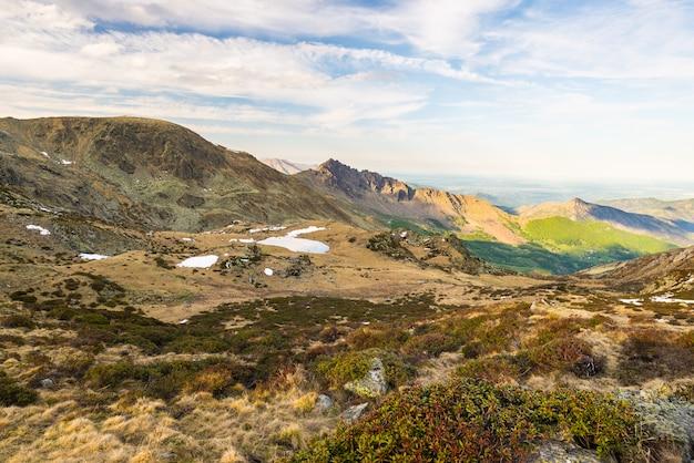 Ultima leggera luce solare sulle cime delle montagne rocciose, creste e valli delle alpi al tramonto