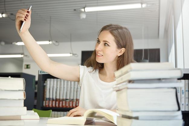Umano e tecnologia. persone ed educazione. ritratto dell'interno della donna adolescente caucasica alla biblioteca che prova a prendere un selfie, circondato da libri e manuali