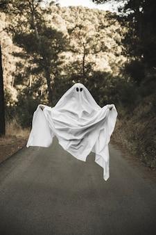 Umano in cupo costume fantasma che vola in campagna