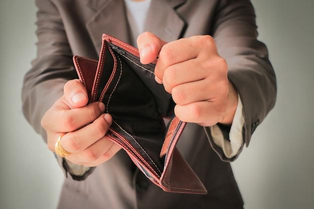 Umano in tuta che mostra il portafoglio vuoto