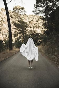 Umano in tuta fantasma che salta sull'itinerario della campagna
