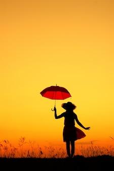 Umbrella donna silhouette in piedi e tramonto