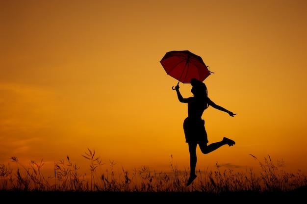 Umbrella salta donna e tramonto silhouette