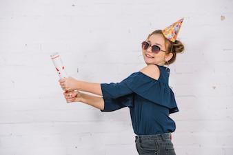 Un'adolescente sorridente che lascia fuori il popper del partito che sta davanti alla parete bianca