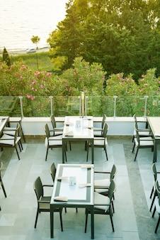 Un accogliente tavolo di vimini nel bar-caffetteria all'aperto sul tetto al mattino con vista su un mare,