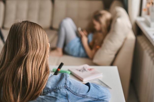 Un'adolescente fa i compiti mentre sua sorella gioca sul suo telefono. comunicazione, distanza sociale durante la quarantena. apprendimento a distanza, istruzione online