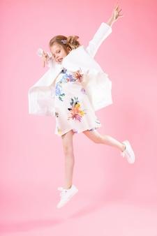 Un'adolescente in abiti leggeri saltò su un muro rosa.
