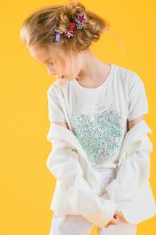 Un'adolescente in vestiti bianchi che posano sul giallo