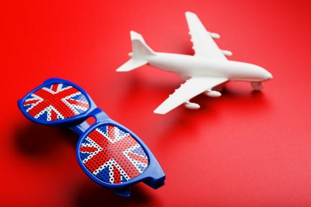 Un aereo passeggeri bianco vola in occhiali da sole con la bandiera del regno unito ,.