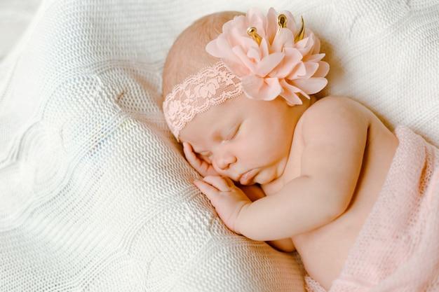 Un affascinante neonato, avvolto in una morbida coperta rosa