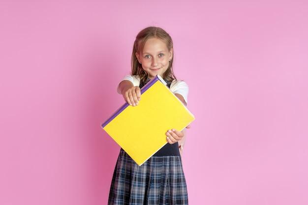 Un'affascinante ragazza con i capelli biondi in un'uniforme scolastica con un libro in mano su uno sfondo rosa.