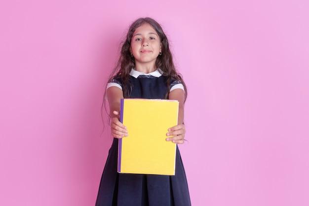 Un'affascinante ragazza con lunghi capelli scuri ricci in uniforme scolastica con un libro in mano su uno sfondo rosa.
