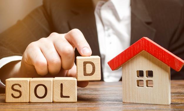 Un agente immobiliare tiene dei blocchi con la parola venduto