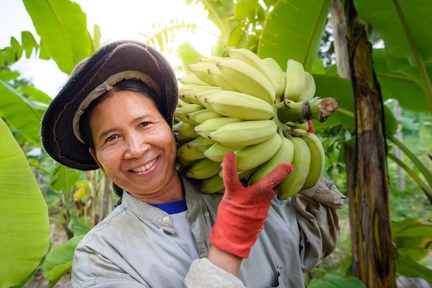 Un'agricoltore asiatica tiene banane crude e raccoglie prodotti nella sua piantagione di banane