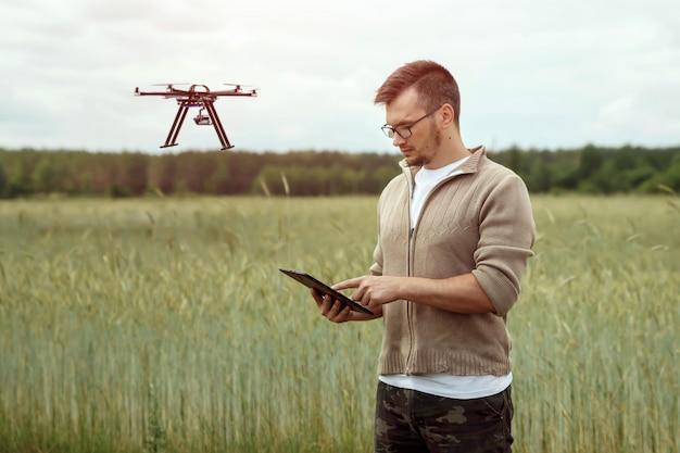 Un agricoltore maschio gestisce un drone su terreni agricoli.