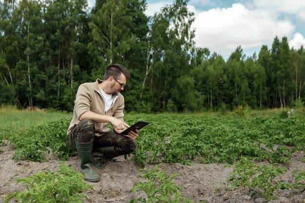 Un agricoltore maschio seduto sul campo e utilizzando una tavoletta. applicazione moderna di tecnologie nelle attività agricole.