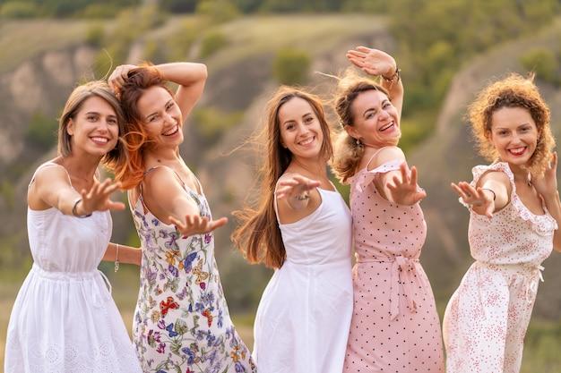 Un'allegra compagnia di bellissime amiche si gode la compagnia e si diverte insieme in un pittoresco luogo di verdi colline.