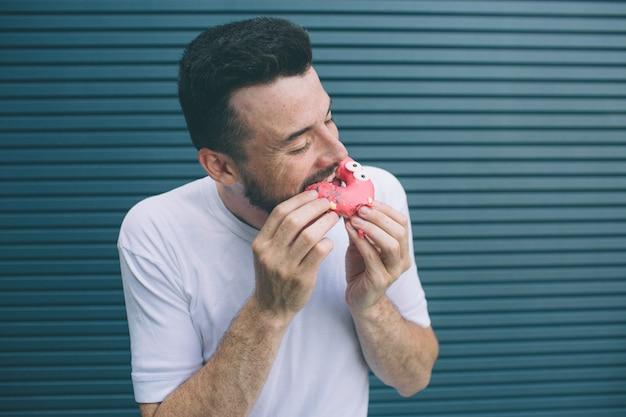 Un'altra immagine dell'uomo che morde un pezzo di ciambella rossa. gli piacciono i dolci. isolato su strisce