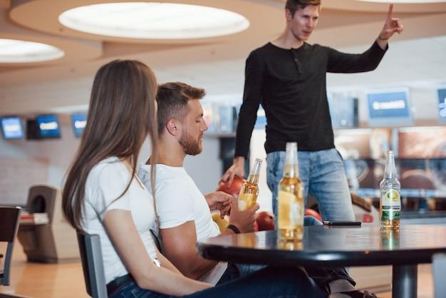 Un altro tentativo per favore. i giovani amici allegri si divertono al bowling durante i fine settimana