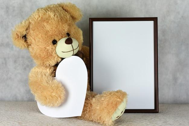 Un amorevole orsacchiotto mantiene una cornice con un cuore nel giorno di san valentino