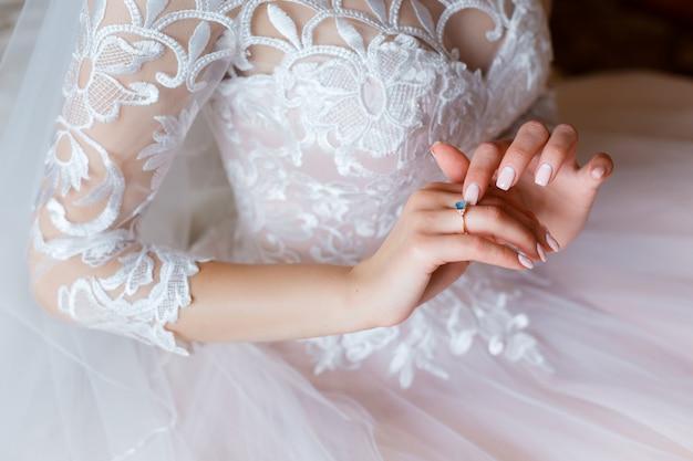 Un anello di fidanzamento in oro con una gemma blu sulla mano della sposa. delicato abito da sposa rosa con corsetto in pizzo