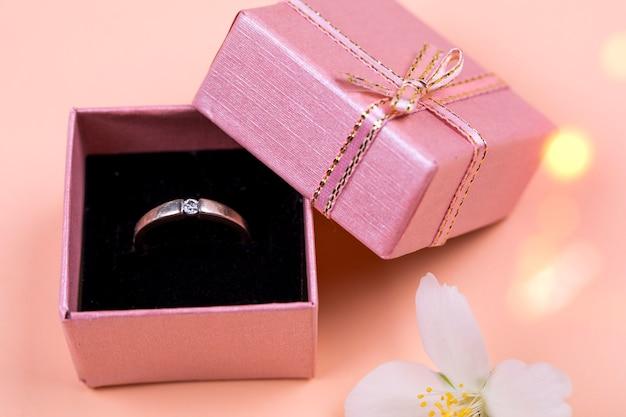 Un anello di weddig in una piccola scatola artigianale su uno sfondo di corallo morbido.
