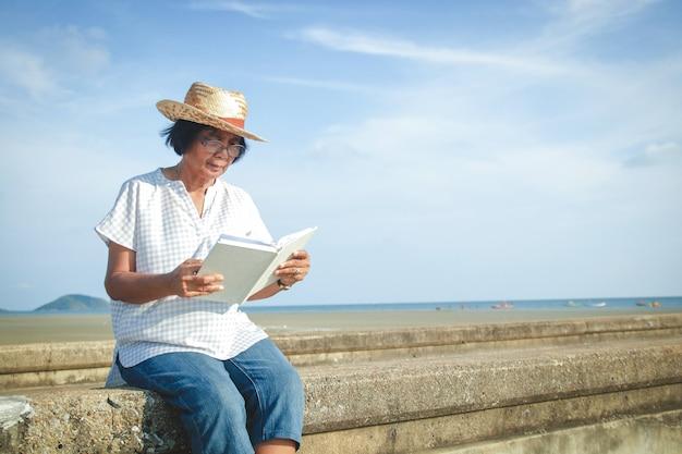 Un'anziana donna asiatica che legge un libro sul ponte di cemento in riva al mare per rilassarsi e respirare aria fresca.