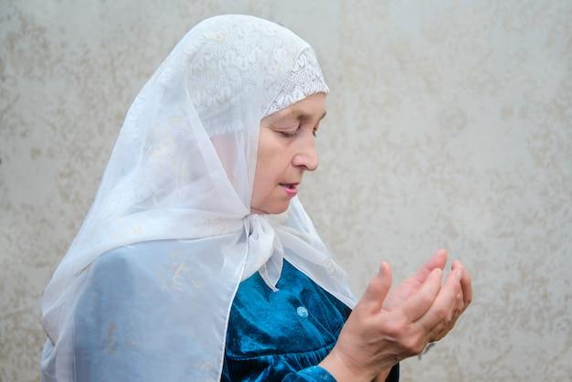 Un'anziana donna musulmana legge preghiere