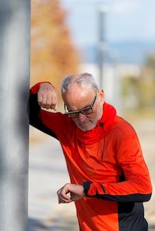 Un anziano attivo da jogging che osserva il suo smartwatch