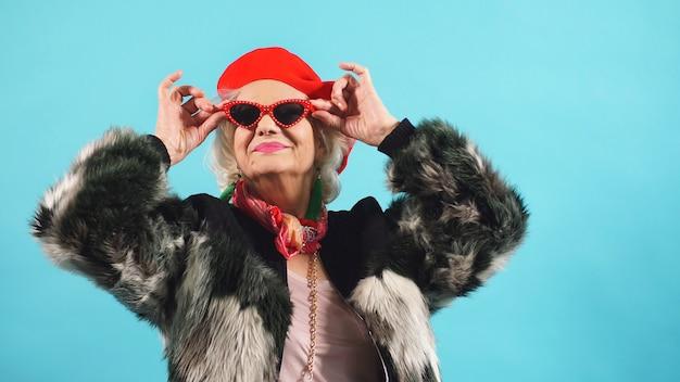 Un anziano pensionato carino in un cappello rosso e occhiali da sole pone