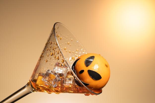 Un'arancia con la faccia di zucca in un bicchiere di martini con ghiaccio e splash.