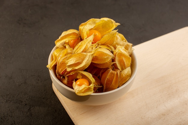Un'arancia di vista frontale fruttifica dentro le bucce e il piatto bianco sullo scrittorio e sul buio di legno